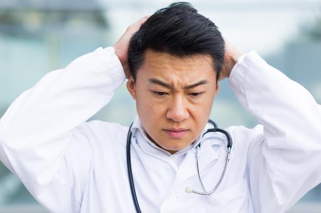 Ritratto di un medico asiatico stanco dopo il lavoro da vicino foto Foto Premium