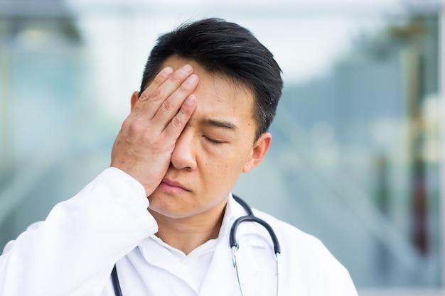 Ritratto di un medico asiatico stanco dopo il lavoro da vicino foto