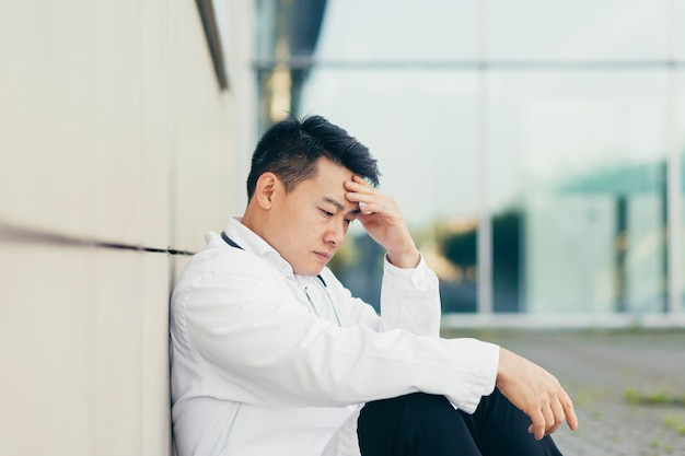 Ritratto medico uomo asiatico stanco dopo il lavoro seduto sul pavimento vicino alla clinica deluso dal risultato