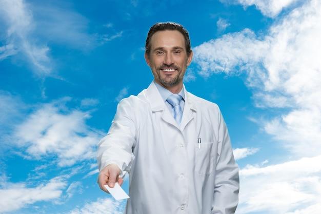 Ritratto del medico che ti dà il suo biglietto da visita. cielo azzurro con nuvole sullo sfondo.