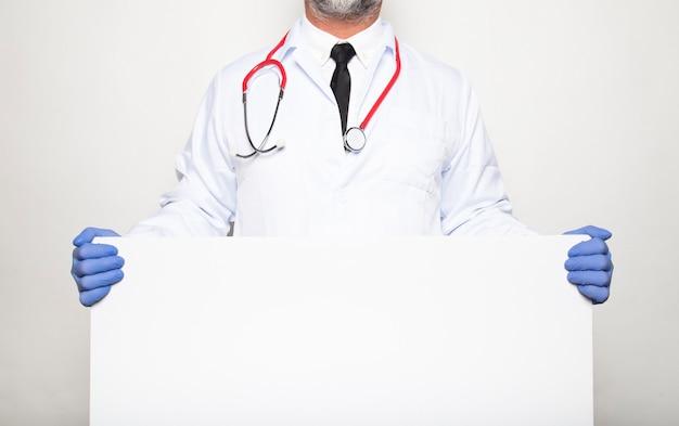Ritratto di un medico che mostra cartello bianco