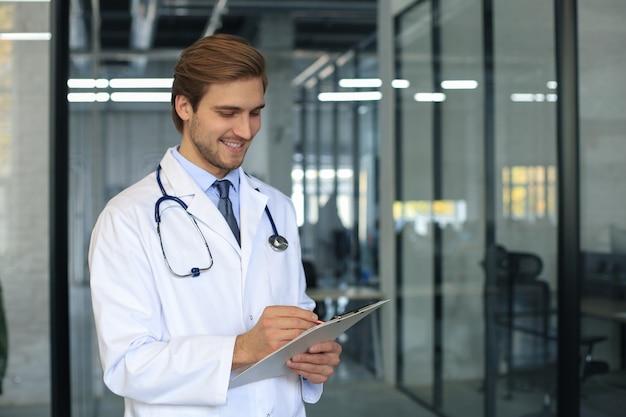 Ritratto di medico in piedi nel corridoio dell'ospedale indossando camice e stetoscopio.