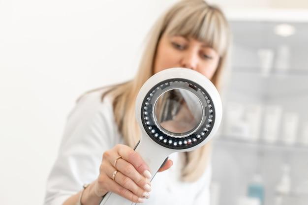 Ritratto di medico tricologo dermatologo guardando un dermatoscopio