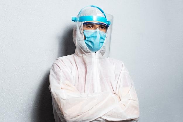 Ritratto di un medico che indossa una tuta dpi contro il coronavirus e il covid-19, sullo sfondo del muro bianco.