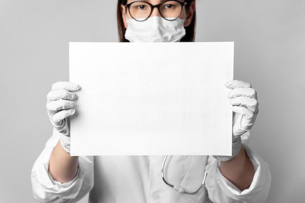 Ritratto di medico con maschera chirurgica con un cartello