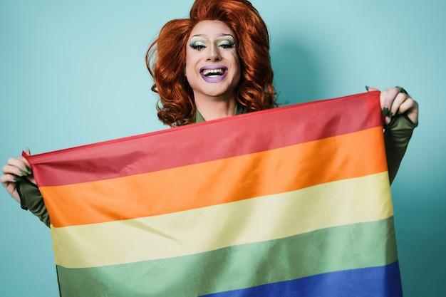 Ritratto di drag queen che tiene bandiera arcobaleno - concetto lgbt - focus on face