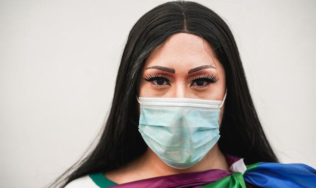 Ritratto di drag queen alla parata lgbt all'aperto con maschera facciale durante l'epidemia di coronavirus