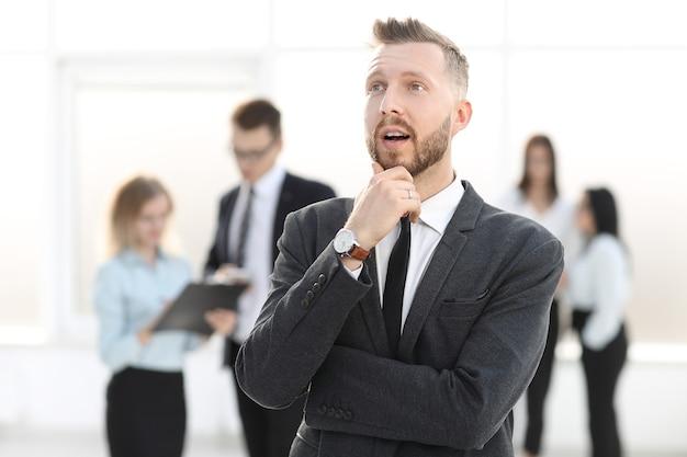 Ritratto di un uomo d'affari di sogno su uno sfondo sfocato di ufficio. concetto di affari
