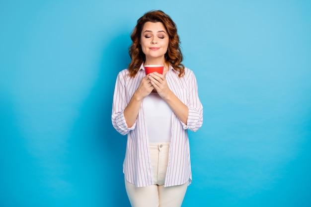 Ritratto di ragazza sognante che beve caffè isolato su sfondo di colore blu