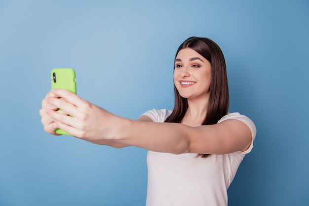 Il ritratto della signora felice sognante tiene lo smartphone prende il sorriso raggiante a trentadue denti del selfie su fondo blu
