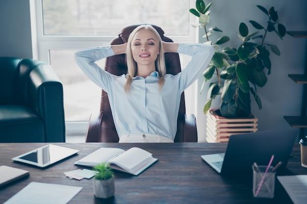 Il ritratto della ragazza professionale sognante si rilassa sul posto di lavoro