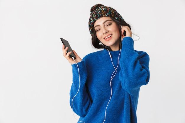 Ritratto di donna estatica che indossa cappello invernale e auricolari tenendo lo smartphone in piedi, isolato su bianco
