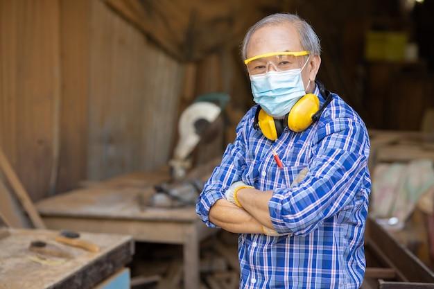 Ritratto di un anziano lavoratore del legno hobby per una buona pensione, maschio asiatico maturo maestro professionista di mobili artigianali in legno creatore di legno uomo.