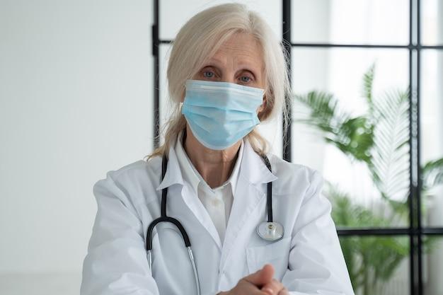 Ritratto di un'anziana operatrice medica con una maschera sul viso in un ufficio in un ospedale