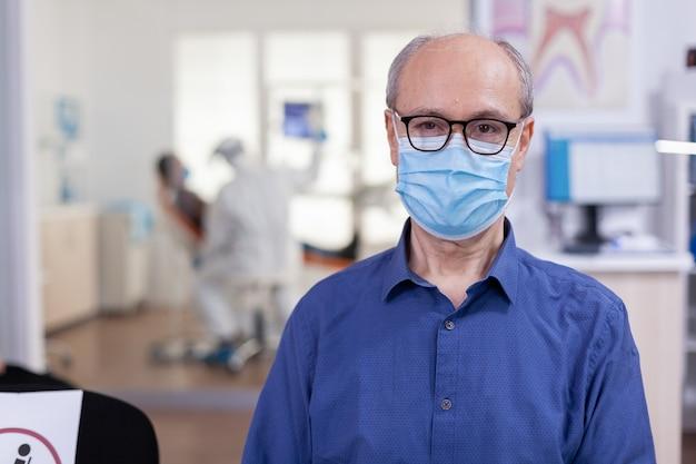Ritratto di uomo anziano in studio dentistico guardando la telecamera indossando maschera facciale seduto su una sedia in sala d'attesa clinica stomatologica