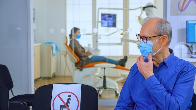 Ritratto di paziente anziano con maschera di protezione che parla seduto su sedie mantenendo la distanza sociale in clinica stomatologica, in attesa del medico durante il coronavirus. concetto di nuova normale visita dal dentista