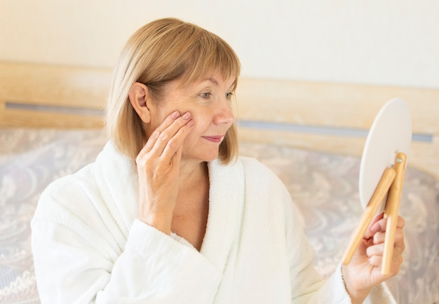 Ritratto di donna anziana nella sua bedrrom. concetto anti invecchiamento, sanità e cosmetologia, vecchiaia, pensionato e maturo