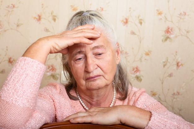 Ritratto una donna anziana tiene la testa con la mano e guarda tristemente in basso