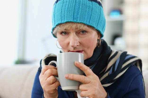 Ritratto di una donna anziana in cappello caldo che tiene tazza con la medicina