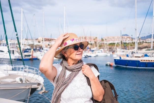 Ritratto di una donna anziana con i capelli grigi e cappello seduto al porto guardando barche a vela