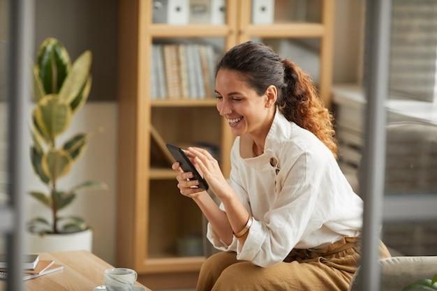 Ritratto di donna adulta elegante guardando lo schermo dello smartphone e ridendo mentre si chatta online con amici e familiari, copia dello spazio
