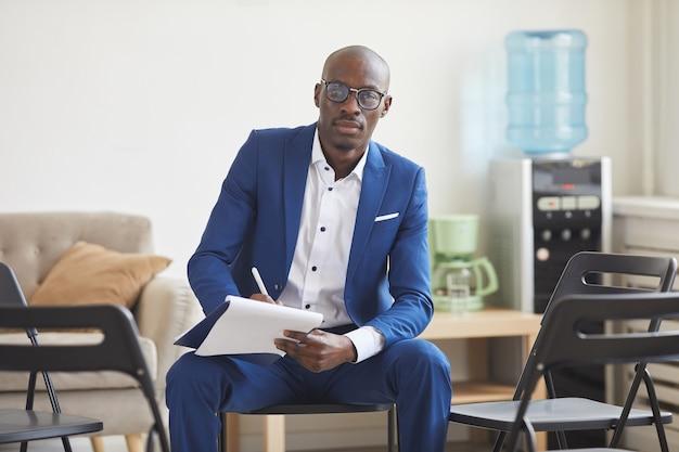 Ritratto di elegante uomo afro-americano che tiene appunti e mentre è seduto su sedie in cerchio per incontro di gruppo di supporto, concetto di psicologo maschio, spazio di copia