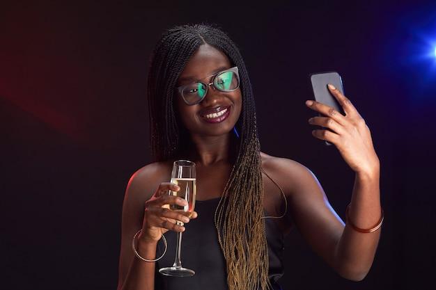 Ritratto di donna afro-americana elegante che tiene il bicchiere di champagne e scattare foto selfie mentre si gode la festa, lo spazio della copia