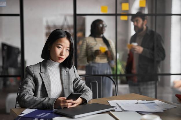 Ritratto di un'elegante donna d'affari asiatica che guarda la telecamera mentre lavora al tavolo in un interno grigio grafico dell'ufficio, spazio copia