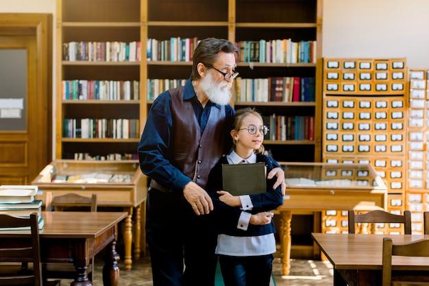 Ritratto di elegante nonno barbuto vecchio con la sua nipote piuttosto sorridente con gli occhiali in piedi insieme e abbracciando in biblioteca e godersi il tempo insieme