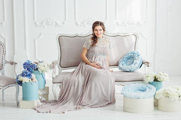 Ritratto di un'elegante bella donna incinta che indossa un abito grigio