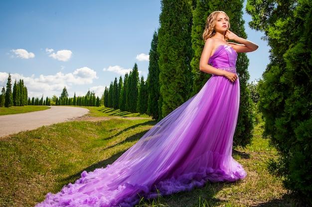 Ritratto di bella donna elegante in abito da principessa con gonna lunga in vicolo verde