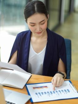 Ritratto di una donna d'affari elegante seduta sul posto di lavoro che guarda e punta il dito sul rapporto d'affari