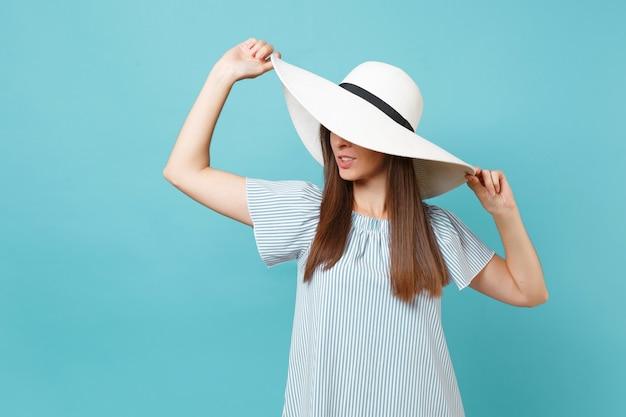 Ritratto di moda elegante bella giovane donna in cappello da sole a tesa larga estate bianca, vestito messo le mani sulla testa, guardando da parte sullo spazio copia isolato su sfondo blu pastello. concetto di stile di vita.