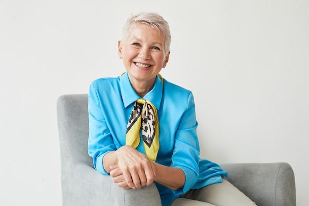 Ritratto di donna matura elegante in bella camicetta blu seduto sulla poltrona e sorride alla macchina fotografica isolata su priorità bassa bianca