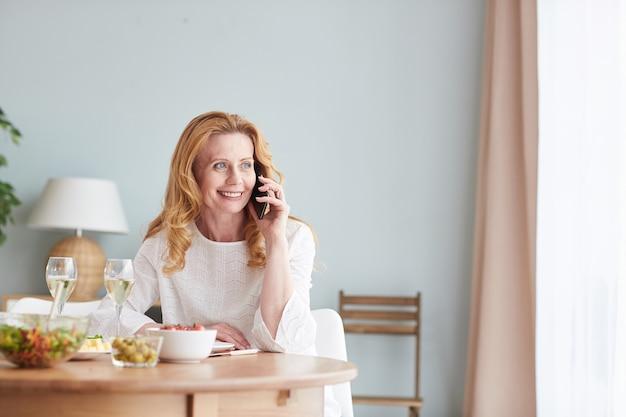 Ritratto di donna matura elegante che parla al telefono mentre si gusta la cena a casa, copia dello spazio