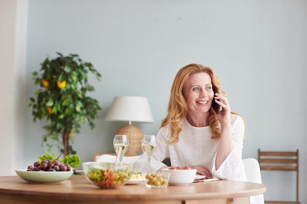 Ritratto di donna matura elegante che parla dallo smartphone mentre gusta la cena a casa o al bar, copia dello spazio