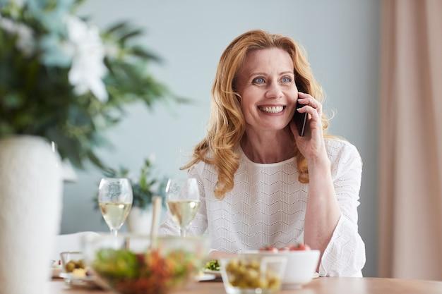 Ritratto di donna matura elegante che parla dallo smartphone mentre gusta la cena a casa, copia dello spazio