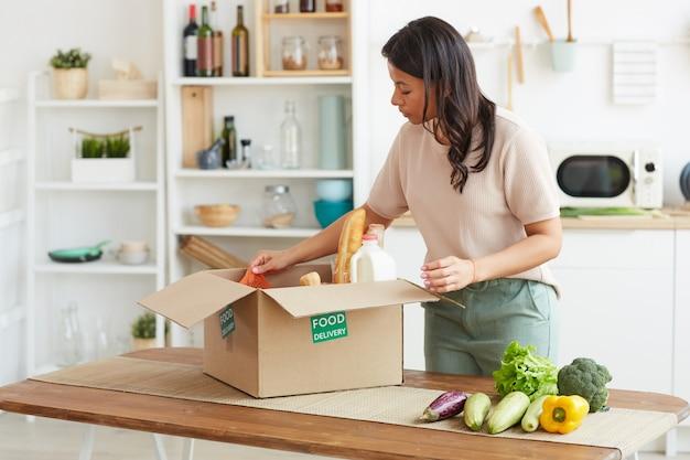 Ritratto di donna elegante di razza mista disimballaggio scatola con cibo mentre si gode la consegna dal mercato degli agricoltori
