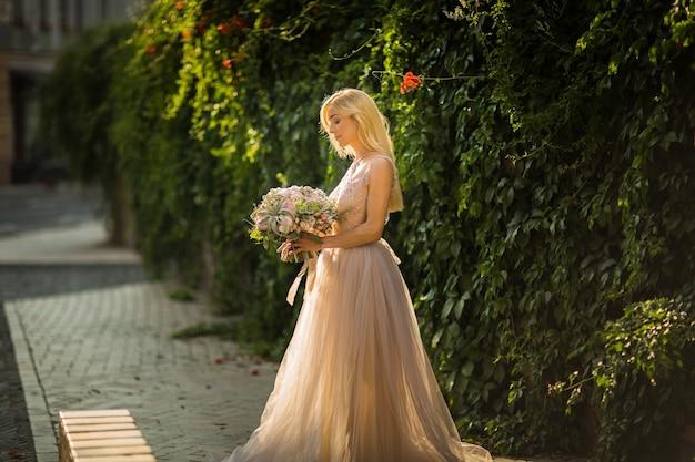 Ritratto di una donna graziosa elegante che indossa l'abito da sposa grigio e posa in strada. la sposa tiene un mazzo di fiori pastello e vegetazione