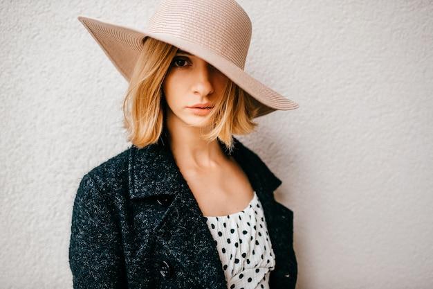 Ritratto di cappello e giacca womanin elegante alla moda capelli corti biondi