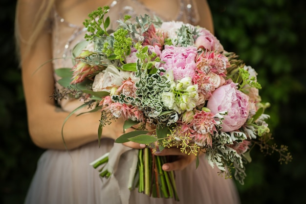 Ritratto di un'elegante donna graziosa irriconoscibile che indossa l'abito da sposa grigio e posa in strada. la sposa tiene un mazzo di fiori pastello e vegetazione