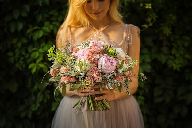 Ritratto di una donna graziosa irriconoscibile elegante che indossa l'abito da sposa grigio e posa in strada. la sposa tiene un mazzo di fiori pastello e vegetazione