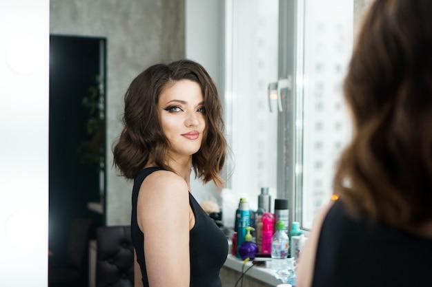 Ritratto di donna elegante con capelli ricci guardando il riflesso nello specchio