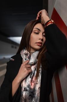 Ritratto elegante giovane donna bruna con pelle pulita con labbra sexy con trucco naturale in cappotto alla moda nero con sciarpa di seta con fiori stampa vicino a un pilastro rosso-bianco. bella ragazza in posa.