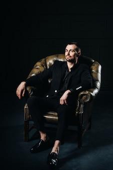 Ritratto di un elegante giovane europeo in abito seduto su una sedia in un interno buio.