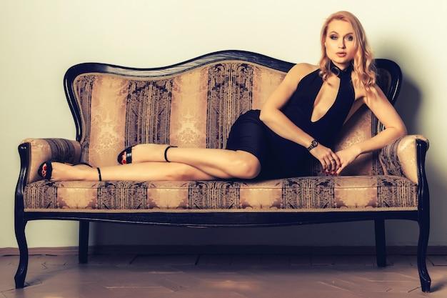 Ritratto di una giovane donna elegantemente bella posa su un divano antico.