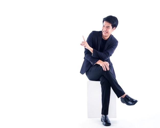 Ritratto dell'uomo bello emotivo che indica il dito contro il muro bianco con lo spazio della copia