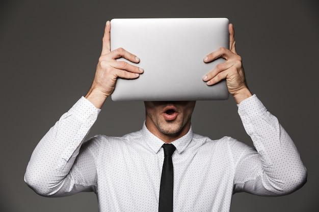 Ritratto di lavoratore di ufficio uomo emotivo in posa tenendo il computer portatile d'argento alla sua testa, isolato sopra il muro grigio