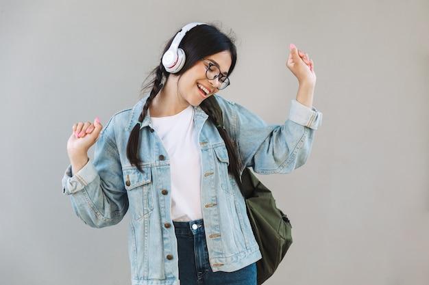 Ritratto di una bella ragazza emotiva in giacca di jeans che indossa occhiali isolati su un muro grigio ascoltando musica con le cuffie che ballano.