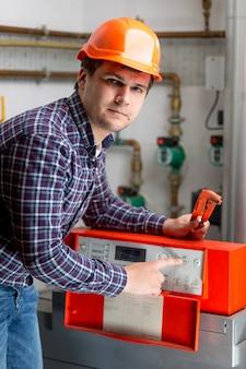 Ritratto di ingegnere che regola il lavoro di riscaldamento sul cruscotto di controllo automatizzato